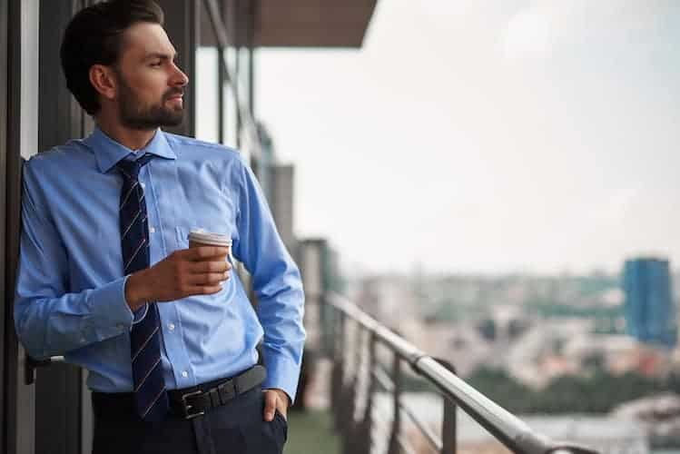 Businessman looking over a downtown balcony.